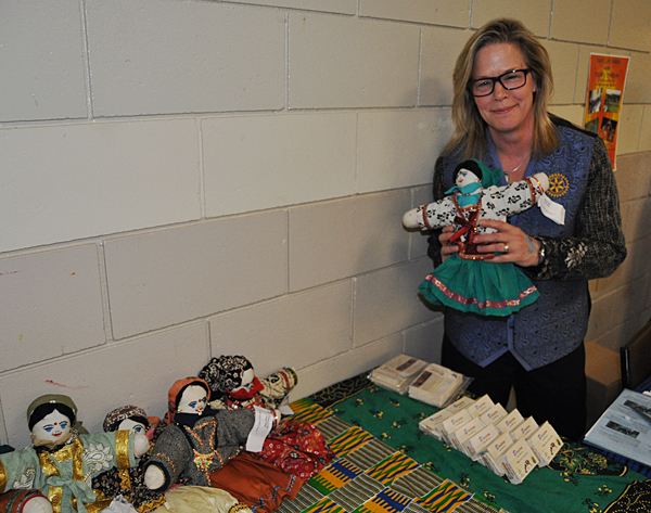 Otti Brown shows off some of the items — adorable dolls and handmade soaps — that were made by children at the GEMS school to raise money for textbooks. David F. Rooney photo