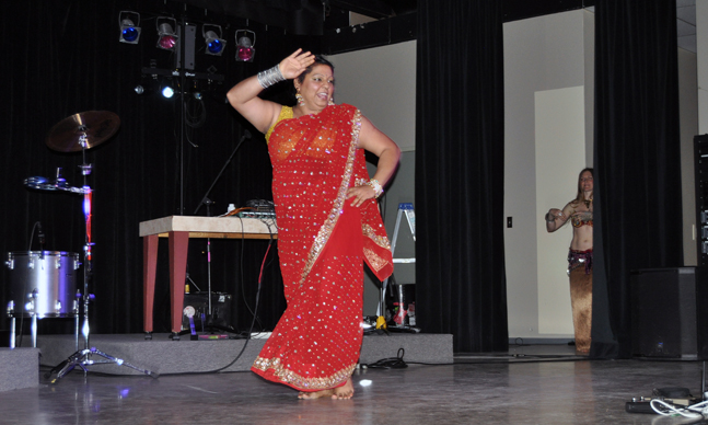 Goldie Sanghera is a woman of many talents. Not only does she run one of the city's most popular restaurants but she can perform traditional dances. That's belly dancer Kimberly Olson watching from the wings. David F. Rooney photo