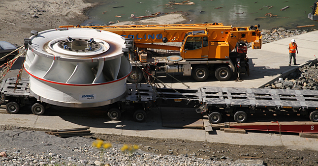 After a journey of almost 13,000 kilometres the German-made turbine for Unit 5 at BC Hydro's Mica Generating Station is guided onto a barge at Valemount for the last stage of its journey. Ron Ross photo courtesy of BC Hydro