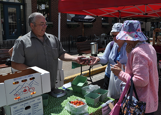 Winfield fruit grower Francis Pequeno offers some of his delicious cherries to a pair of customers on Saturday. The fresh cherries proved to be very popular with shoppers.  David F. Rooney photo
