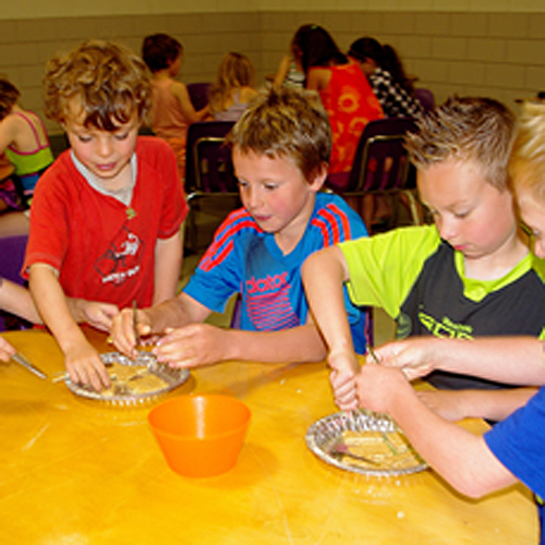 Kids at the library's Summer Reading Club event called Insect Mania had a chance to not only look at bugs up close and personal but how to eat like them, too, as thesde young boys are intent on doing. Lucie Bergeron photo