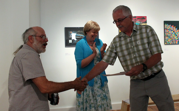 Visual Arts Society Chairman Ken Talbot hands volunteer Rod Aspeslet a certificate of appreciation for helping install the gallery's new flooring. Jewelles Smith photo