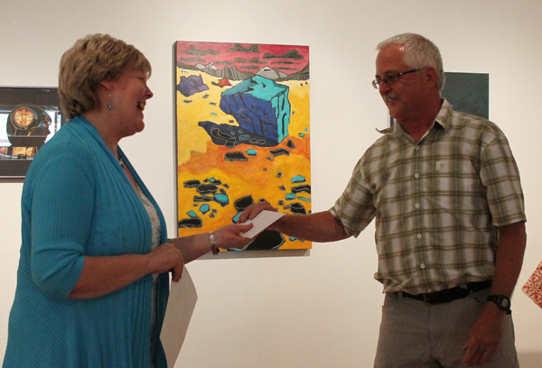 Jackie Pendergast, executive director of the Revelstoke Art Gallery, hands Ken Talbot, the Visual Arts Centre's chairman and hard-working volunteer, a certificate of appreciation for his work installing the gallery's new flooring. Jewelles Smith photo