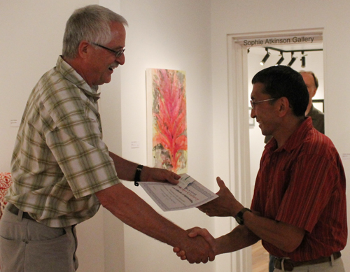Visual Arts Centre Chairman Ken Talbot hands fellow artist and volunteer Mas Masutsushita a certificate of appreciation for his work installing the art gallery's new flooring. Jewelles Smith photo