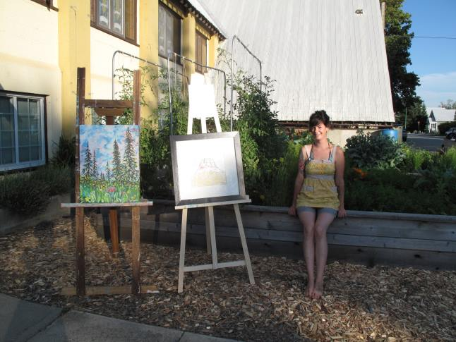 NCES urban junior farmer Sara Jeffries welcomes visitors at the Community Garden alongside paintings by Rachel Kelly and Kimberly Olsen. Laura Stovel photo