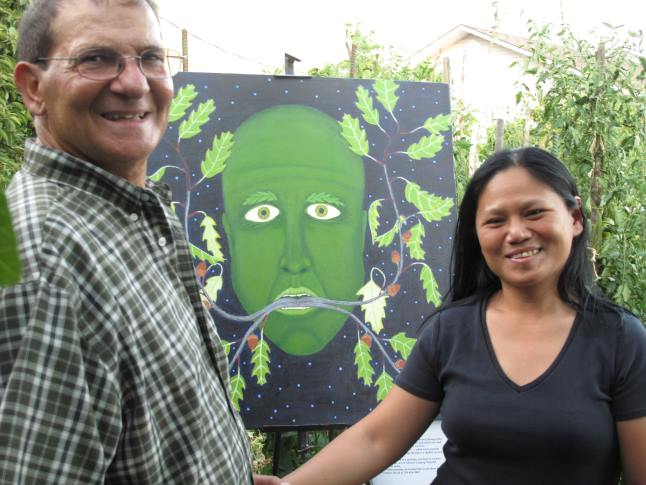 Guiseppe and Laarni. Iaccino welcome David Rooney's fitting painting, The Green Man, to their beautiful garden. Guiseppe spends three to four hours a day in his garden. He grows nectarines, peaches, pears, apples, figs (Yes, he has two full grown fig trees(, tomatoes, leeks, peas, beans, peppers, cabbage, egg plants, soy beans and other fantastic crops. Laura Stovel photo