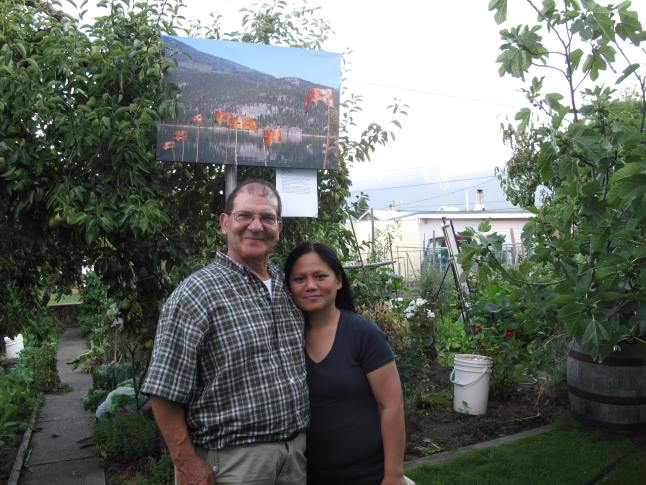 Guiseppe and Laarni pose in front of their garden. The image above them is a photo of a environmental work by David Rooney called Spirits of the Forest that was installed at Blanket Creek Provincial Park back in 2011. Laura Stovel photo