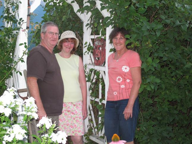 Ceramic artist Kat Mather (right) tucks a beautiful mask into the arbor of gardeners extraordinaire Bob and Cheryl Willford. Laura Stovel photo