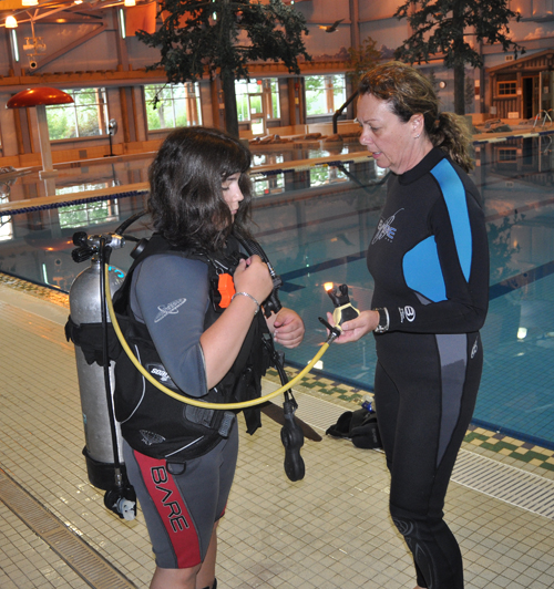 Novice diver Alicia Kindret gets a helping hand from Frieda Boyd during the first-ever dive class offered at the Aquatic Centre. David F. Rooney photo