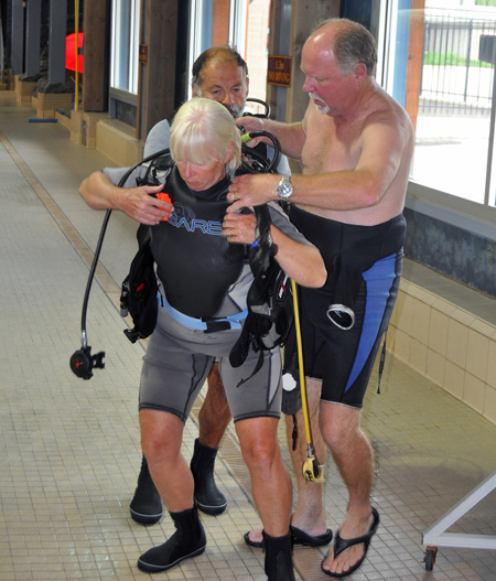 Diving instructor Sheldon Boyd (right) helps diving student Elizabeth Kozak shrug into the harness fo her diving tank. David F. Rooney photo