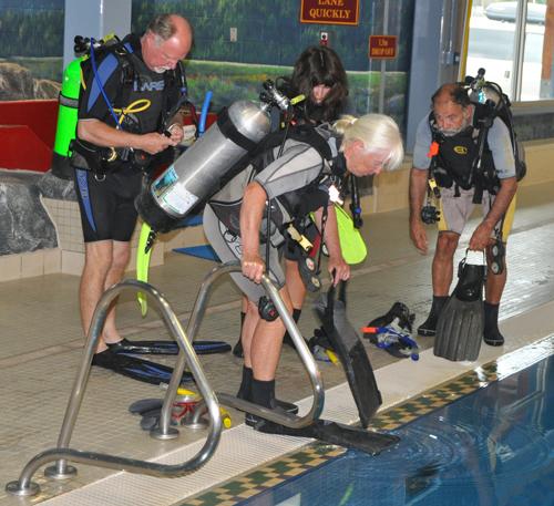 Elizabeth, her husband Brian (right) and Alicia put on their swim fins as Boyd (left) checks his regulator. David F. Rooney photo