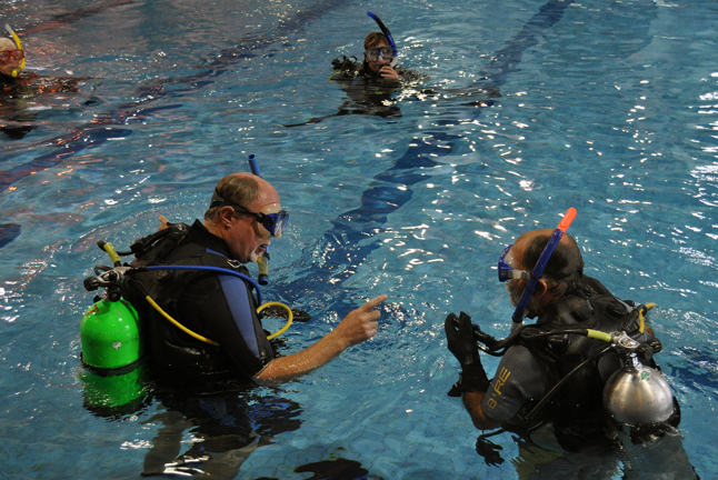Instructor Sheldon Boyd (right) tells student Brian Kozak that he should't work too hard while underwater. Straining the body will sap your energy and use up your allotment of air faster than if you take your time to accomplish your tasks underwater. David F. Rooney photo