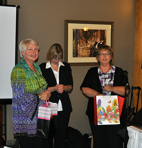What's coming out of the bag? Tracy Spanner and Linda Chell, who worked very closely with Anne on Revelstoke's Early Childhood Learning Programs, had a gift for her. David F. Rooney photo