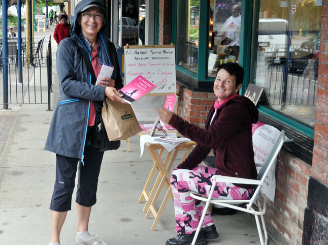 Author DebiLyn Smith hands a copy of her book, Running from Cancer: a titled memoir, to a customer outside Grizzly Books on Friday, August 23. Smith's book describes her efforts to come to terms with a breast cancer diagnosis. You can read more about her book here: https://legacy.revelstokecurrent.com//2013/08/22/new-book-describes-ways-to-come-to-terms-with-a-cancer-diagnosis. If you'd like to purchase a copy of it you can buy one from DebiLyn today at Grizzly Books. She is there until 4 pm. David F. Rooney photo