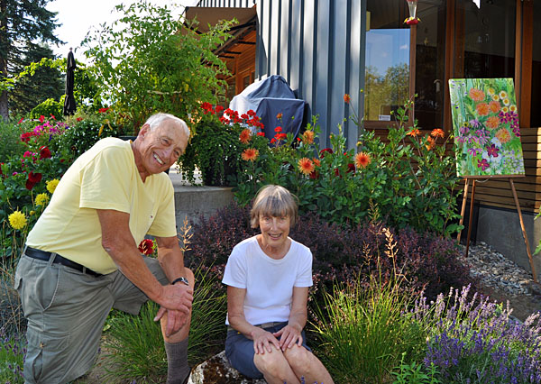 Geoff and Gwen pose in their garden with one of Jackie Pendergast's lovely silk paintings. David F. Rooney photo