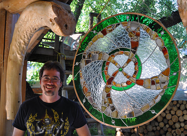 Geordie Knoess poses with a new stained glass work into which he has integrated translucent agates. He and his partner, painter and sculptress Barbara Maye combne their sense of art with their garden on Oscar Street. David F. Rooney photo