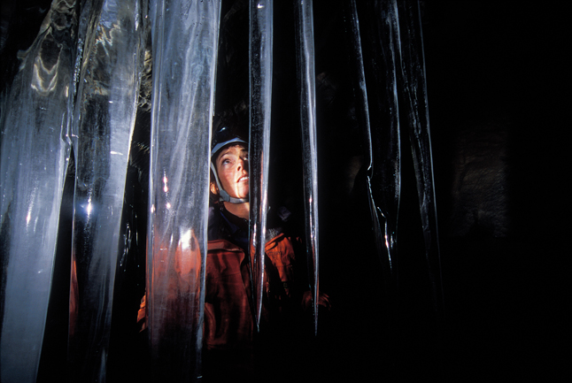 Sylvia Forest wonders at the beauty of an icicle curtain inside the caves. Rob Buchanan photo courtesy of Parks Canada