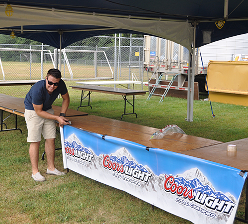 Molson-Coors rep Tanner Henning tapes a role of advertising to the front of the main bar at the Rotary Club's Beer Garden. And, yes, that reefer in the background is FULL of beer and coolers destined to quench ball players' thirst this long weekend. David F. Rooney photo