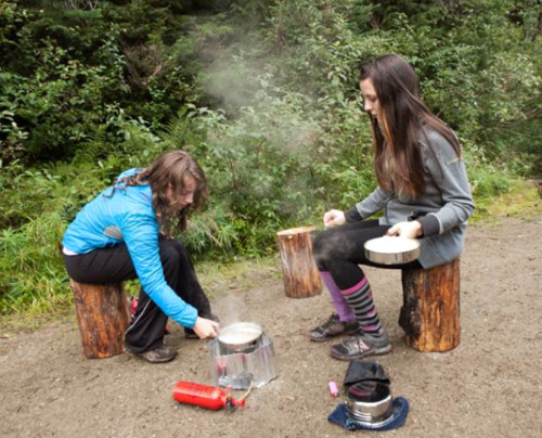 Maxine Opatril and Emma Knight Flood work together to make dinner outside.  Alice Weber photo courtesy of Parks Canada