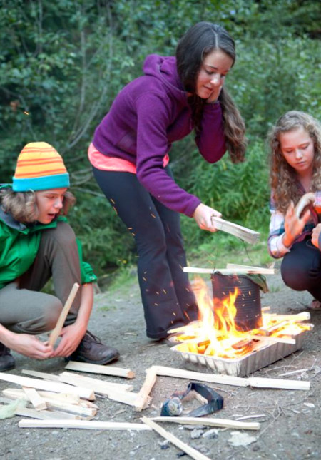 Learning how to light a fire and boil water is an important wilderness skill. Winners of the GASP Flint and Steel/Fire-Building/Water Boiling Race: River Kelly, Anne-Marie Duschene, Sara Howatt, (missing from photo: Wyatt Callaghan). Natalie Harris photo courtesy of Parks Canada
