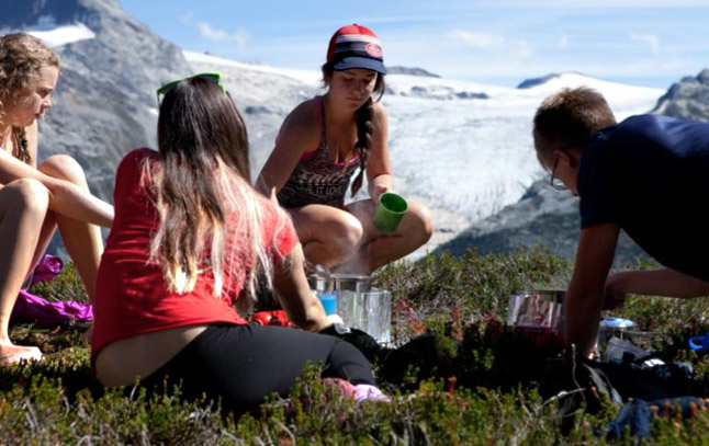 Sara Howatt, Anne-Marie Duschene, Mackenzie Mallet and Emma Knight Flood (back) practice lighting their camp stove and making a hot lunch safely in the alpine. Natalie Harris photo courtesy of Parks Canada