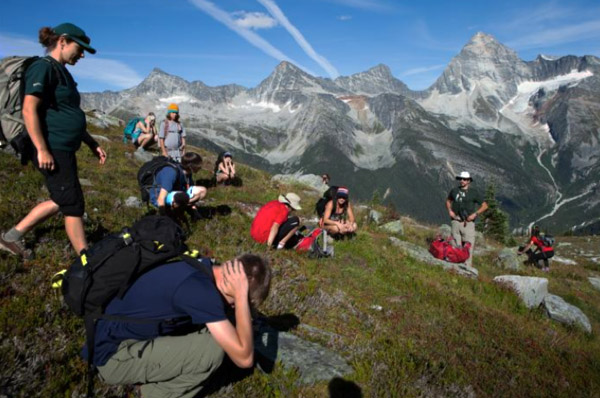 What happens if lightning strikes? Alice Weber and Matt Keeler watch on as students practice valuable lessons in how to avoid lightning in the alpine. Crouch down by a large rock, cover your head, heels together and stay low. Natalie Harris photo courtesy of Parks Canada