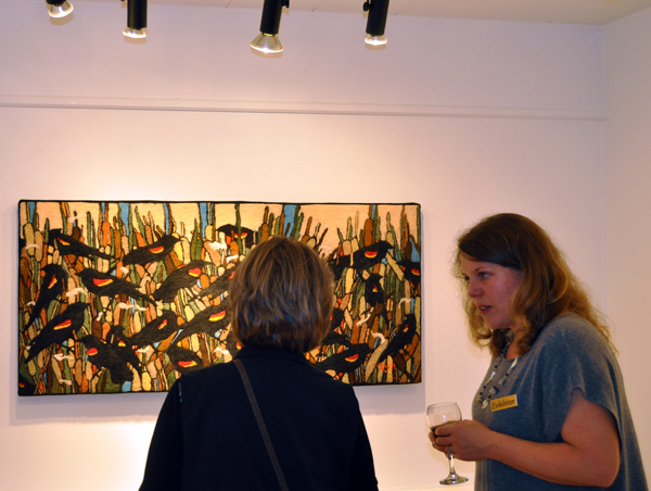 Kaslo artist Robin Wiltse (right) talks with a gallery visitor about her spectacular needle and hand-fleted wool work, Redwing Blackbirds and Cat Tails, during the opening of her show at the Revelstoke Arts Gallery last Friday. David F. Rooney photo