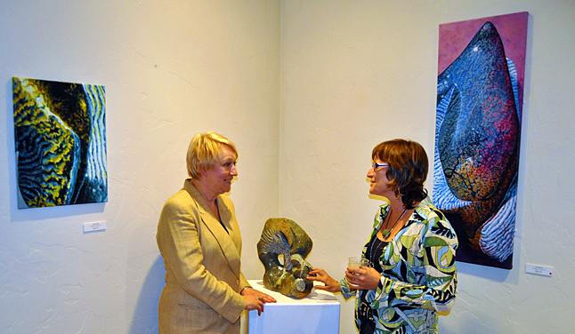 "NAKUSP — Revelstoke artist Barbara Maye (right) chats with Anne Beliveau, owner of this village's Studio Connexion gallery during the opening of Pigments, an exhibition of Barbara's newest paintings and sculptures. These particular works are Release (left), Patience (a sculpture hand-carved from Zimbabwean soapstone) and Stamina. Both Release and Stamina are acrylics on canvas. Barbara lived in Nakusp before moving to Revelstoke a couple of years ago and is well-known in the village's artistic community. Originally from Quebec, Beliveau has lived in Nakusp for 35 years and has reputation for finding and nurturing local artists as well as bringing well-known painters and sculptors to town. Dozens of local art lovers attended the opening and Anne Beliveau said she and Barbara pleased by the number of people who showed up. ""After you left we had a couple from England, 2 people from Toronto, 2 from Kamloops and one from Winnipeg,"" told me in an e-mail on Saturday morning. ""Art lovers are amazed by Barbara's colourful paintings and her sculptures. Her 4th exhibition at Studio Connexion and she still is pushing boundaries."" It's glorious to see that fine art is celebrated everywhere in our region. If you plan on being in Nakusp over the next two weeks you'll be able to view Barbara's show until october 12. Studio Connexion is located at 203 Fifth Avenue NW and is open Tuesdays through Saturdays from 11 am until 4 pm. For more information call 250-265-8888 or visit the gallery's website at http://www.studioconnexion.com. David F. Rooney photo"
