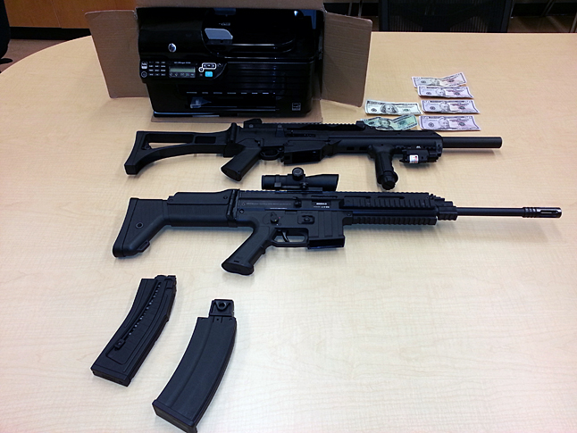 """Here is a photo with respect to the firearms, munition and counterfeit money seized siezed during a raid on two houses by Revelstoke RCMP.  The guns are ISSC Modern Sporting Rifle MK22-caliber.  They were modified to shoot automatically.  The money was in denominations of $100s, $50s and $20s.  Approximately $500 was seized.  """"Our investigation is continuing,"""" Cpl. Thomas Blakney told The Current on Monday.""""We are looking into other reports of other businesses being victimized."""""""