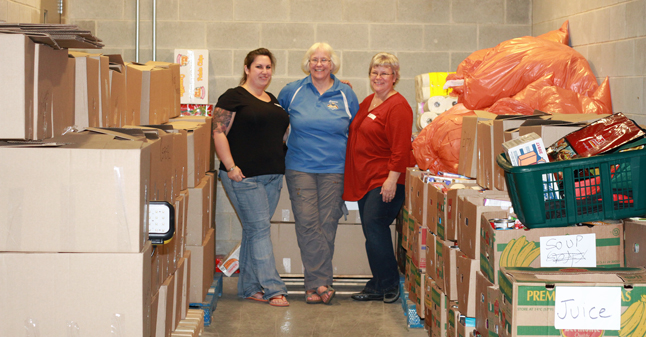 Patti Larson (right) and Krista Carnegie pose with then-Staff. Sgt Jacquie Olsen in the storage area at the RCMP detachment where the 9,054 pounds of food from last year's Emergency Services Food Drive was stored. Carnegie, hopes this year's total will hit 10,000 pounds of food. Revelstoke Current file photo