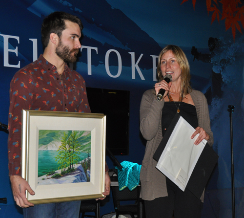 There was also a silent auction. In this image, Amy Flexman describes this painting by local artist Cecilia Lea, held for the audience's view by JP Maurice. David F. Rooney