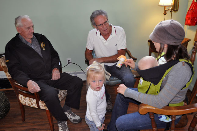 Master Gardeners Sam Olynyk and John Campbell answer a few questions from Erin Wilkins whose daughter, Olive, was mesmerized by the photographer. David F. Rooney photo