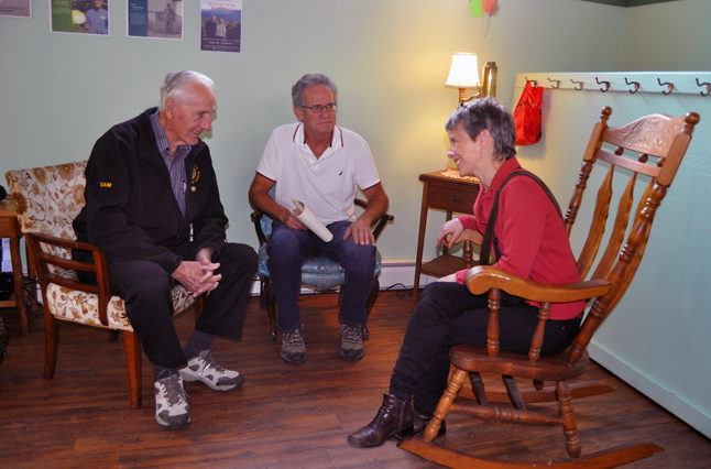 Sam Olynyk (left) and John Campbell enjoy a chat with Laura Stovel. Both master gardeners figure in Laura's book, which she is writing for the North Columbia Environmental Society. David F. Rooney photo