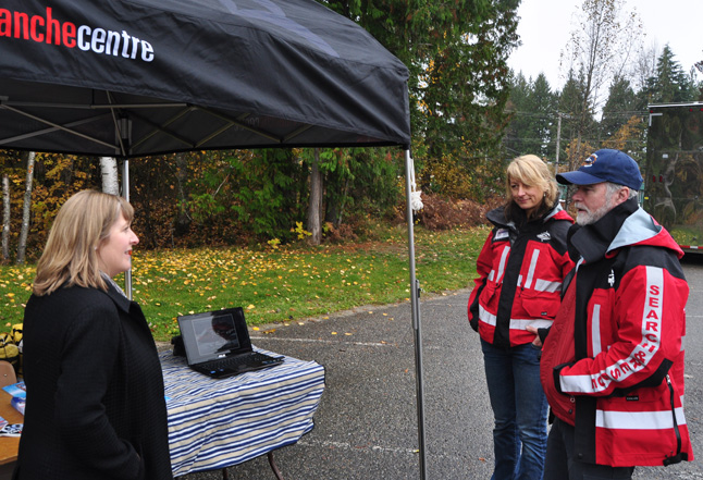 Queen Victoria Hospital Manager Julie Lowes (left) talks with Zusana Driediger and Buck Corrigan of Revelstoke's Search and Rescue unit in the hospital parking lot. Driediger and Corrigan had set up a table and were answering the questions of people attracted to the public display of medical technology in the province's Mobile medical Unit. David F. Rooney photo