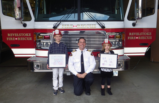 Summer Novakowski of Columbia Park Elementary school and Rider Stockman of Begbie View Elementary School possw with Fire Chief Rob Girard after winning this year's Fire Chief for a Day Contest. Summer and Rider's fire safety posters, illustrating their knowledge and understanding of kitchen fire safety, were chosen from among 124 submissions by loical school children. The two kids were picked up at school on Monday, November 4, in Fire Engine No. 1 and spent the afternoon as the City's Fire Chiefs. Fire Chiefs Novakowski and Stockman received a tour of the fire hall, fire truck rides, prize packages and participated in fire department activities. The two young Fire Chiefs were then treated to lunch with the Fire Chief and Career Firefighters. Assistant Fire Chief Roger Echlin photo courtesy of the Revelstoke Fire Rescue Service