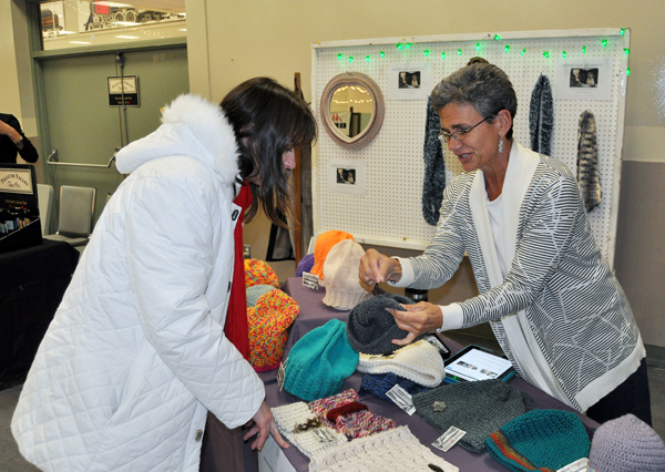 Susan Teuton talks with a potential customer about the handmade hats and other products she was selling at the Hand-Made Parade at the Community Centre on Saturday. The annual craft show is also open on Sunday until 3 pm, so if you're in need of original Christmas gifts then you;d better hustle down there. David F. Rooney photo