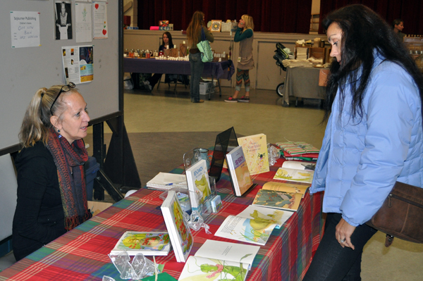 Local author Mieke Blommestein (left) talks with Grizzly Books proprietor Vanessa Smith at the Hand-Made Parade on Saturday. Mieke has just published a new book for Children called, Ben the Crocodile. David F. Rooney photo