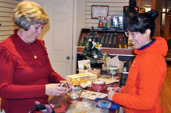 """Deenie Ottenbreit finalizes a purchase by Ashley McCrae as she enjoys her last Moonlight Madness event as a business owner. """"Next year I'll be on the other side of the counter,"""" she laughed. David F. Rooney photo"""