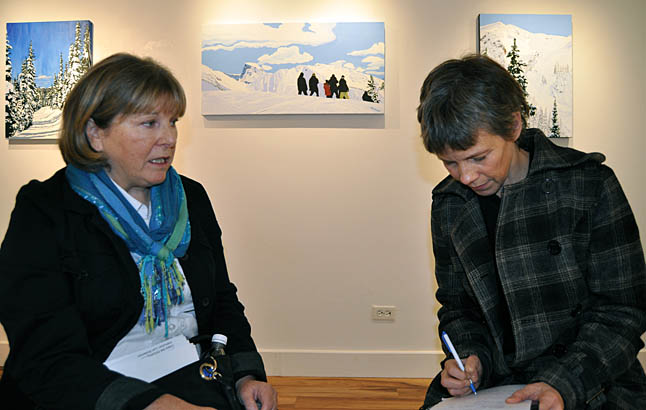Julie Kozek's acrylic paintings, inspired by skiing on a spring day at Revelstoke Mountain Resort, are so vivid that the viewer can vicariously feel the moment, smell the balsam trees and bask in the sunshine just by looking at them. In this photo, Julie is being interviewed by Laura Stovel. David F. Rooney photo