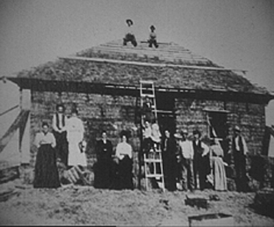 Straw bale construction began at the turn of the 20th. century in the Sandhills region of Nebraska. Homesteaders lacked both trees and sods to build their homes so they used their recently invented balers to produce meadow hay bales to stack as wall material. The bales were laid like bricks, pinned together with wood stakes and the roof was built directly on the walls. The weight of the roof compressed the walls during a one to two month settling period. After the walls stabilized in height, the builders plastered the walls with adobe, lime plaster or traditional lime cement stucco. This is the traditional Nebraska or load bearing method of straw bale construction that flourished in this region until the 1940s when it was replaced by stud frame building. In the early 1980s, builders in Quebec and New Mexico began to experiment with baled fibre construction. Research sponsored at this time by the Canadian Mortgage Housing Corporation determined plastered two string straw bale walls had an R-value of 35, nearly twice that of a conventional stud wall and fire tests gave the stucco plastered bales a two hour fire rating which is the equivalent to the requirement for commercial buildings. Historical photo courtesy of Habib John Gonzalez / Sustainable Works