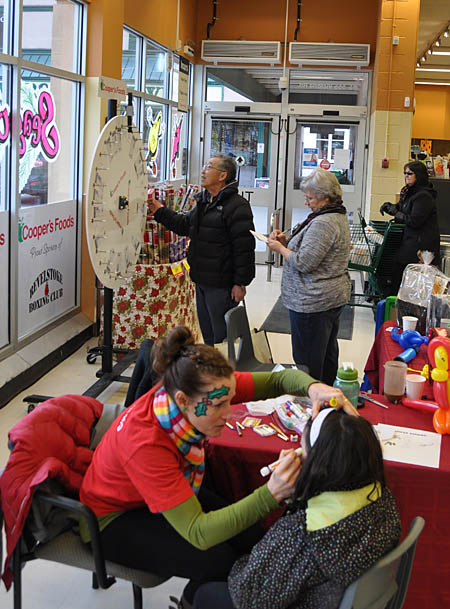 Tom Sakamoto checks to see what his spin of the Wheel of Fortune won for him at Cooper's on Saturday, November 23 as a  child gets a lovely face painting.  Shoppers lined up to make donations to the Community Connections Food Bank and spin the wheel for a chance to win a lovely gift basket. Food Bank coordinator Patti Larson said the wheel saw a lot of action. David F. Rooney photo