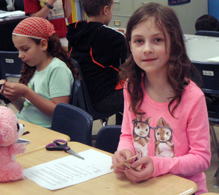 Ava Keerak from Gr. 4/5 smiles brightly as she continues to work on her mouse. Photo by Alice Dunkerson caption by Amelia Brown AHE Student Reporter-Photographers