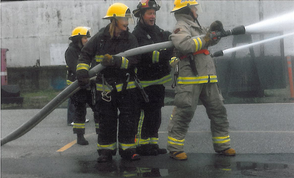 Welock (right) is at the head end of a powerful hose during the three-hour training program. Photo courtesy of Revelstoke Professional Firefighters Local 1746