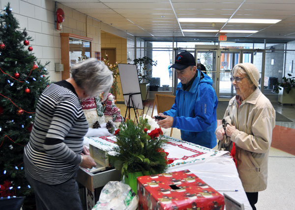 Margaret Pacaud makes change for David Threatful and his mum at the door to this year's Crime Stoppers No Host Bazaar. There were 61 vendors at this event, which made it the largest bazaar of the season. David F. Rooney photo