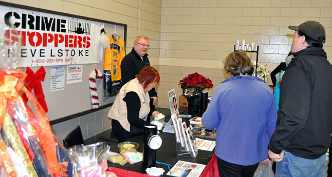 Crime Stoppers member Dave Holtman (center left) talks with a browser at the group's tble inside the Community Centre's Multi-Porpose Room. The group's well-organized No Host Bazaar was a hit this season. David F. Rooney photo