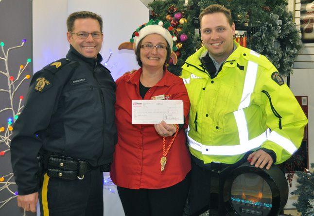 Staff Sgt. Kurt Grabinsky (left) gets an introduction into local generosity as Home Hardware Manager Sheryl Hermansen offers him and Const. Gary McLaughlin a cheque for $250 raised by store employees selling smokies. The money will go towards the Trees for Tots charit that s heavily supported by the RCMP. David F. Rooney photo