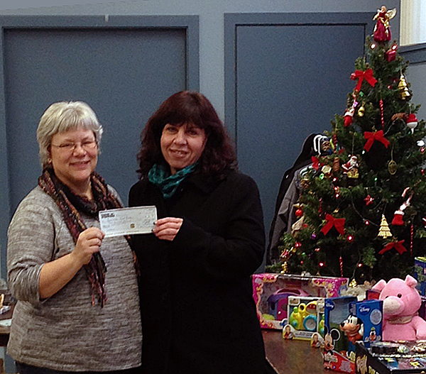 Community Connection Food Bank Coordinator Patti Larson had another good reason to go to the Christmas Hamper Deport on Friday, December 20. With Christmas looming on the horizon Crime Stoppers President Roberta Ciolli (right) dropped by with a cheque for $300 and 100 lbs of food raised during the group's very successful No Host Bazaar.