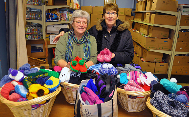 The contents of these five baskets represent the commitment, love and hard work of four local women who have spent hundreds of hours knitting 100 children's slippers, mittens, gloves, hats and scarves. The money to purchase all of that yarn was collected in piggy banks that Carol Sakamoto (center right with Food Bank Coordinator Patti Larsom) placed at local stores. This annual effort by local people truly embodies the Spirit of Giving. These items will be distributed through the  Community Connections Food Bank's Christmas Hamper program. David F. Rooney photo