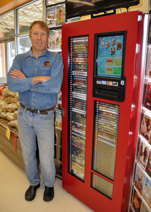 Dave Kaegi poses with his new Columbia River DVD kiosk at Coopers. David F. Rooney photo