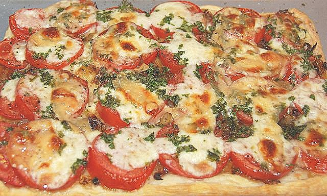 This pizza on puff pastry base consists of just tomatoes, onions, cheese and fresh basil..
